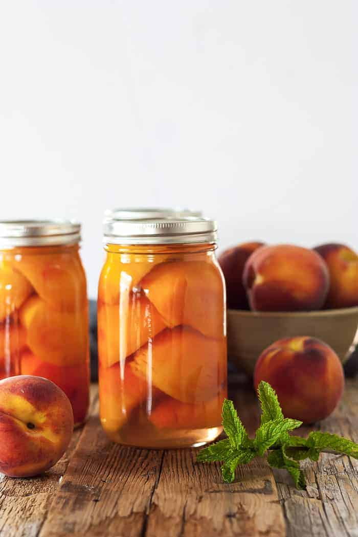 3 jars of canned peaches with mint and a bowl of peaches