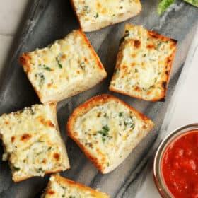 cheesy garlic bread with herbs and marinara sauce on a grey board
