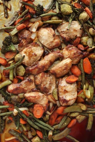 roasted teriyaki chicken and grilled veggies on a rimmed baking sheet
