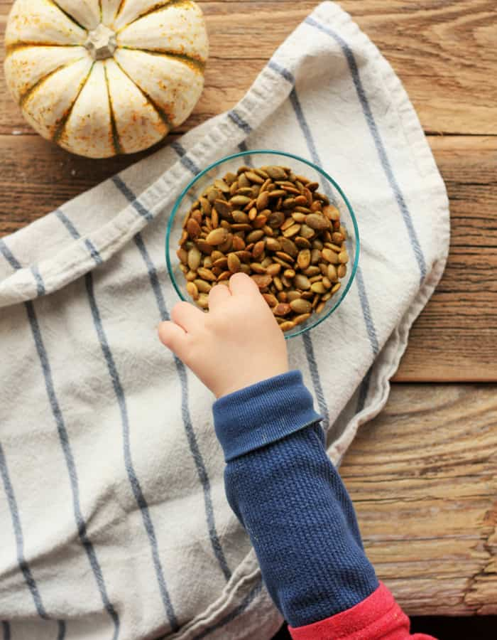 A toddler's hand reaching for a bowl of white cheddar salted pumpkin seeds