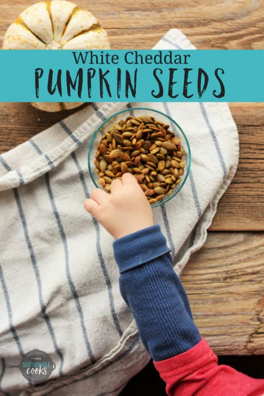 A toddler's hand grabbing a bowl of white cheddar salted pumpkin seeds
