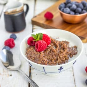 a white bowl of chocolate quinoa topped with berries