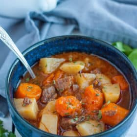 Instant pot beef stew in a blue bowl with a spoon and a grey cloth