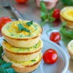 three mini quiche appetizers on a plate with tomatoes and herbs