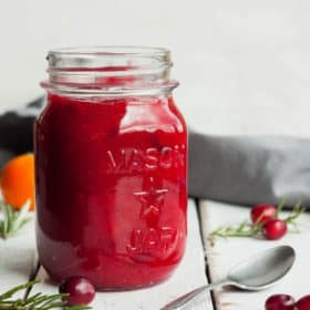a jar of orange cranberry sauce with a spoon and cranberries on a white board