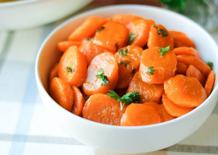 Sliced carrots with parsley in a white bowl