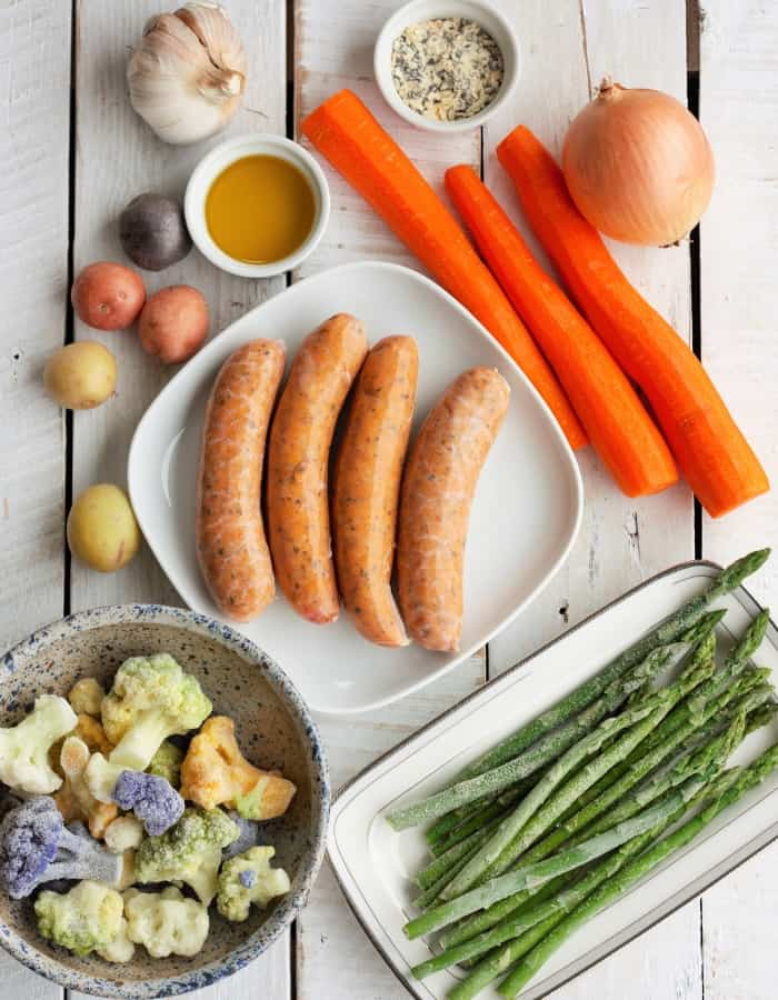sausage, carrots, asparagus and other ingredients on a white board