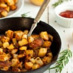 skillet fried potatoes in a cast iron skillet with rosemary and ketchup
