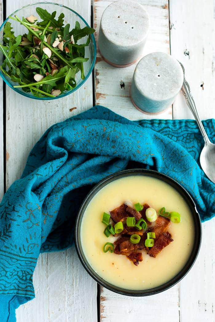 A bowl of whole30 potato soup with a blue cloth and a bowl of green salad