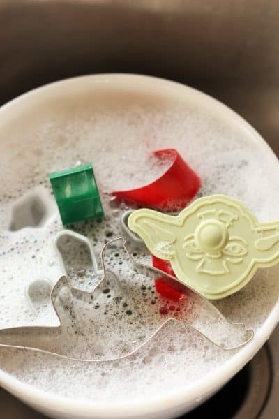 cookie cutters in a bowl of soapy water