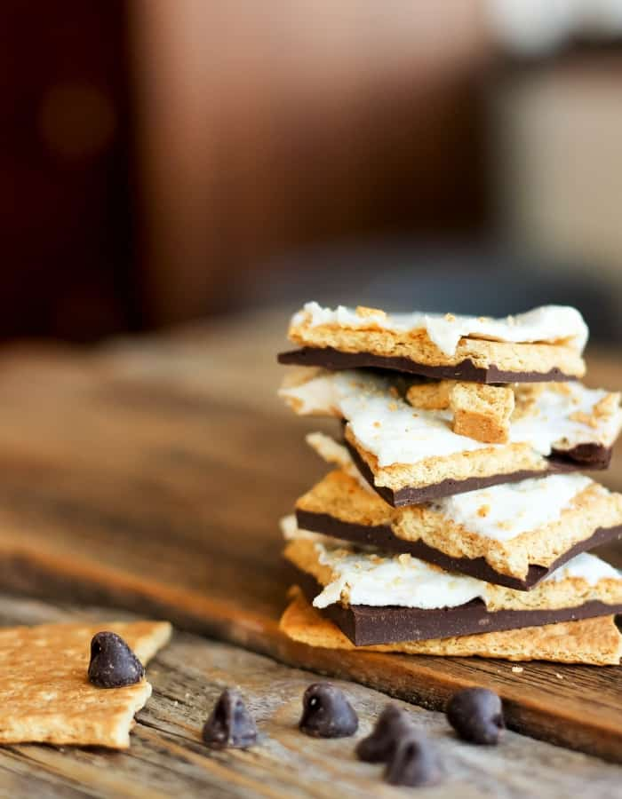 A stack of homemade s'mores bark on a wooden board