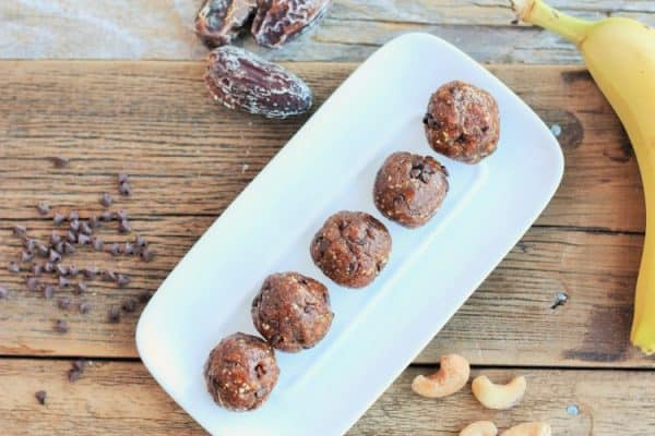 chocolate chip banana bread energy bites on a plate with chocolate chips, dates, and bananas