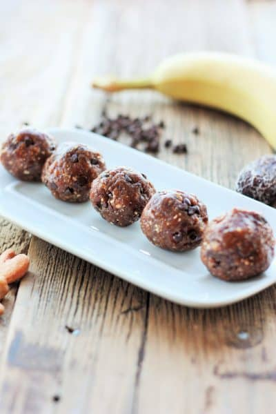 Chocolate Chip Banana Bread Energy Bites on a plate with a banana in the background