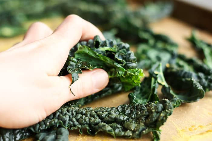 a hand massaging kale for cheesy kale chips