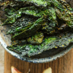 a bowl of cheesy kale chips with garlic