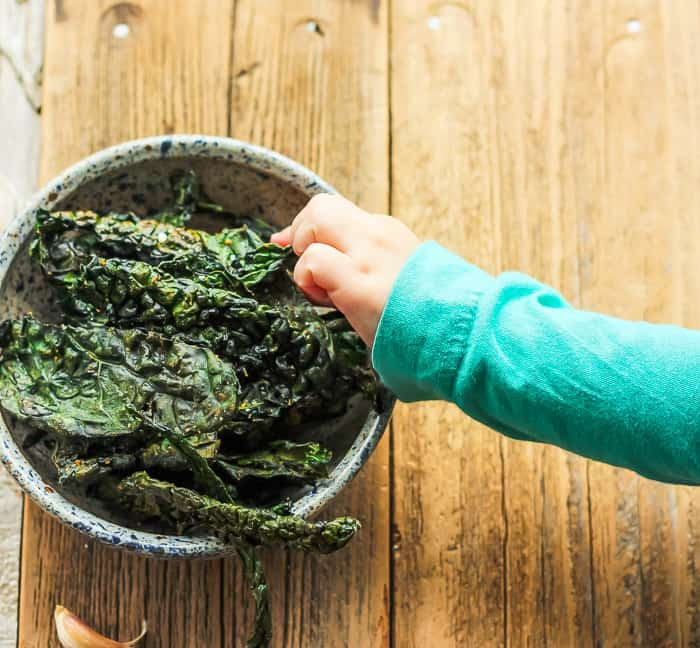 a child's hand reaching into a bowl of cheesy kale chips