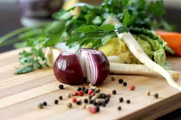 onions and other vegetables on a wooden cutting board