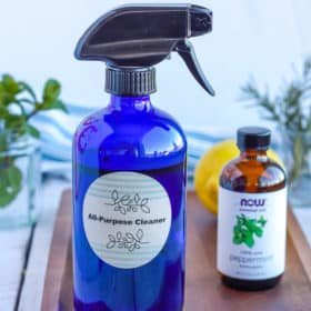 a bottle of homemade all-purpose cleaner on a wooden tray with essential oils, lemon, and fresh mint