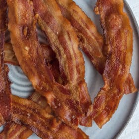 slices of cooked bacon on a grey plate