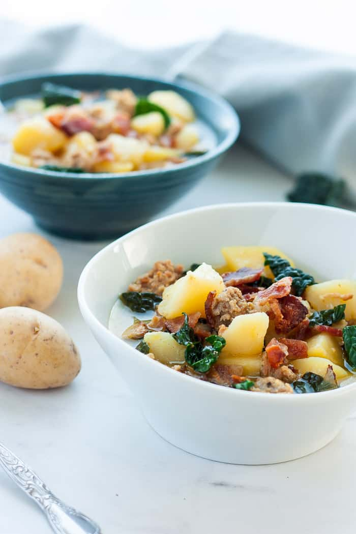 two bowls of dairy-free whole30 zuppa toscana with potatoes and kale on a white table