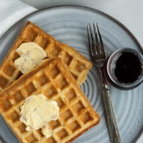 whole grain waffles on a grey plate with a fork and syrup