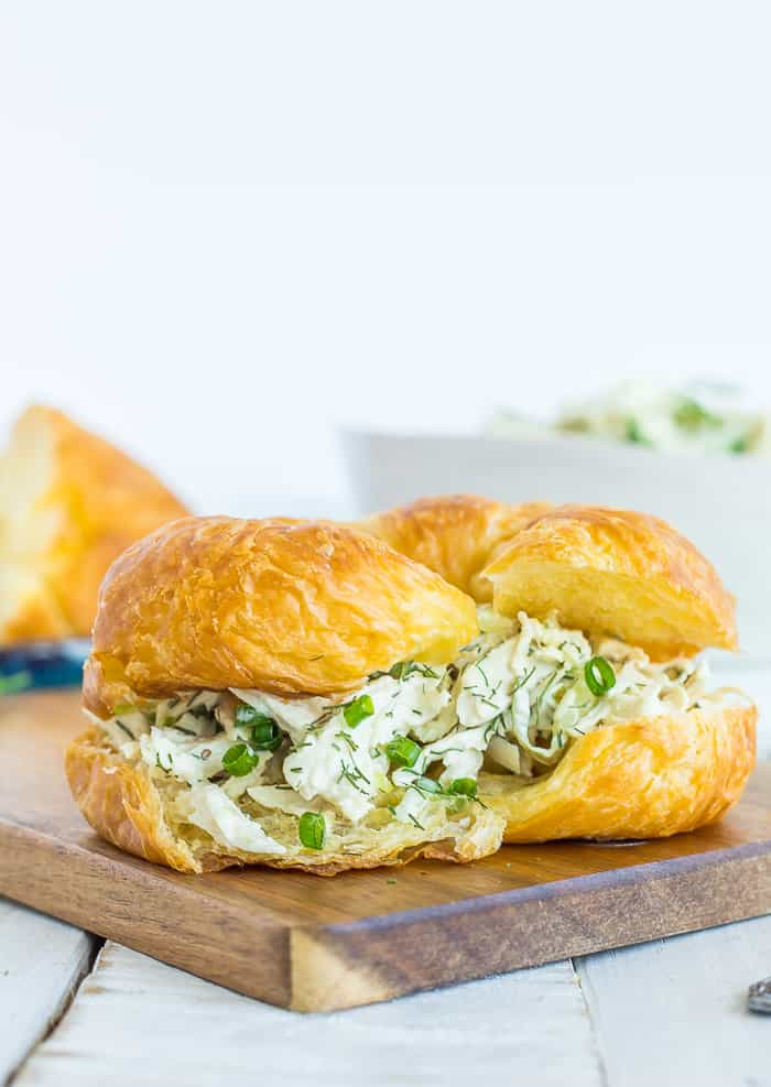 Dill chicken salad on a crossiant on a wooden board