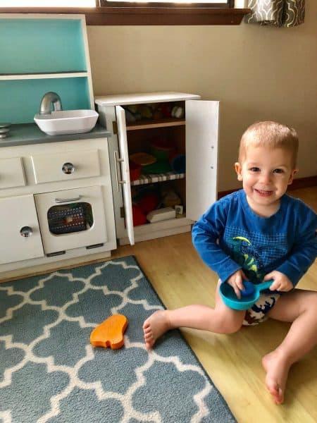 boy in homemade play kitchen