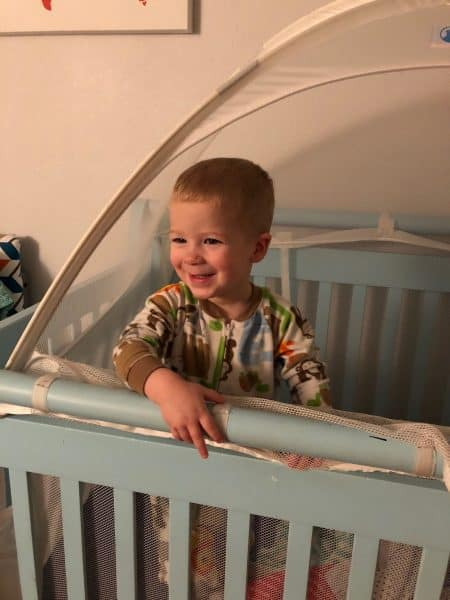 smiling toddler in a crib