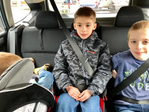 three kids in the backseat of a car
