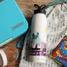 A yumbox lunchbox, liberty bottlesworks waterbottle, and mason jar on a wooden background