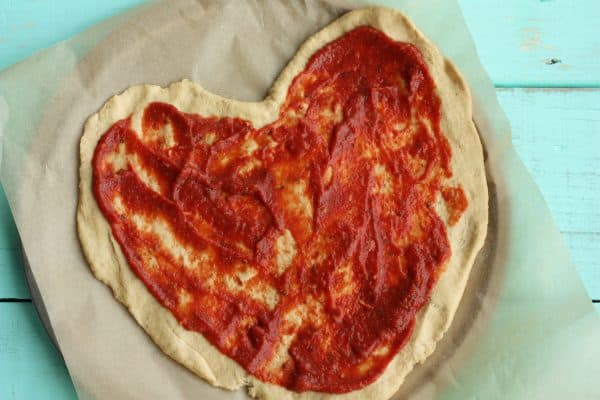 heart-shaped pizza with red sauce