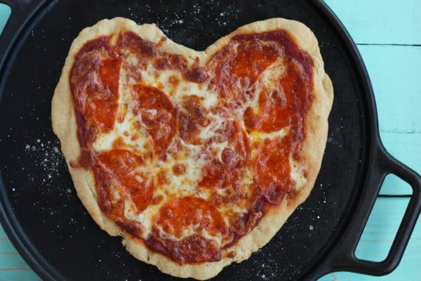 heart-shaped pizza on a cast iron pizza pan
