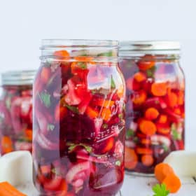 3 jars of pickled encurtido and vegetables on a white board