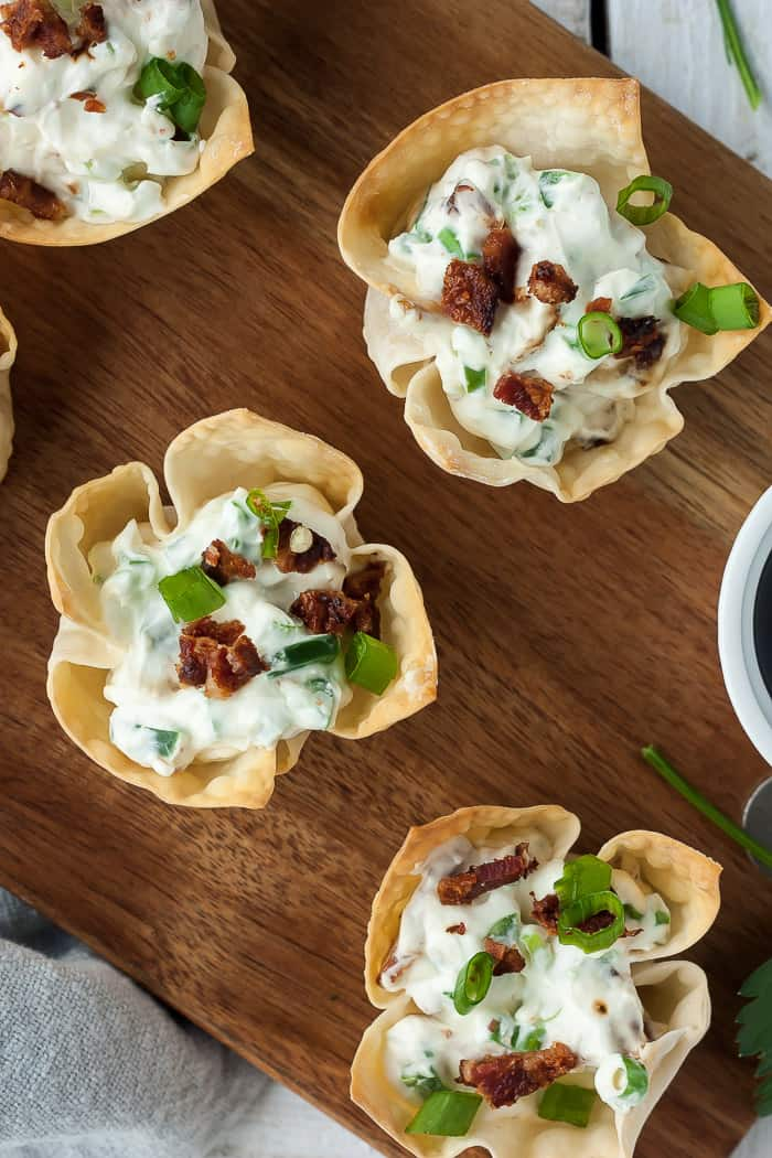 three jalapeno popper wontons on a wooden cutting board
