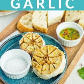 Instant Pot roasted garlic on a blue plate with a dish of salt