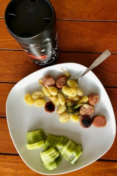 coffee, gnocchi, sausage, and kiwi on a plate
