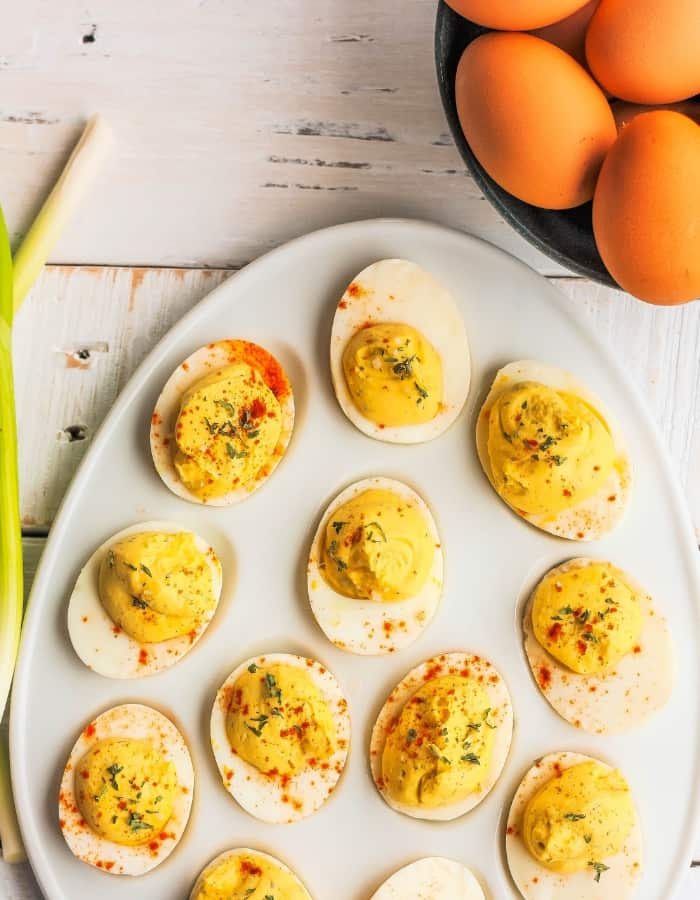 a tray of easy deviled eggs with a bowl of eggs on a white board