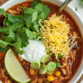 Instant Pot tortilla soup in a bowl with cilantro, sour cream, cheese, lime, and green onion