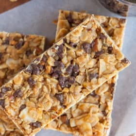 Three granola bars with chocolate chips on a piece of parchment