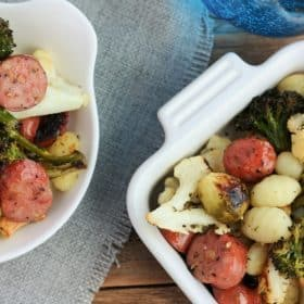 fried gnocchi and roasted veggies in two white dishes with a gray cloth and blue glass of water on a wooden background