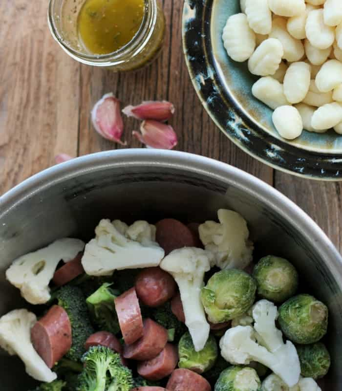 A bowl of frozen vegetables and chicken sausage and a bowl of uncooked gnocchi along with a mason jar of homemade italian dressing and garlic cloves