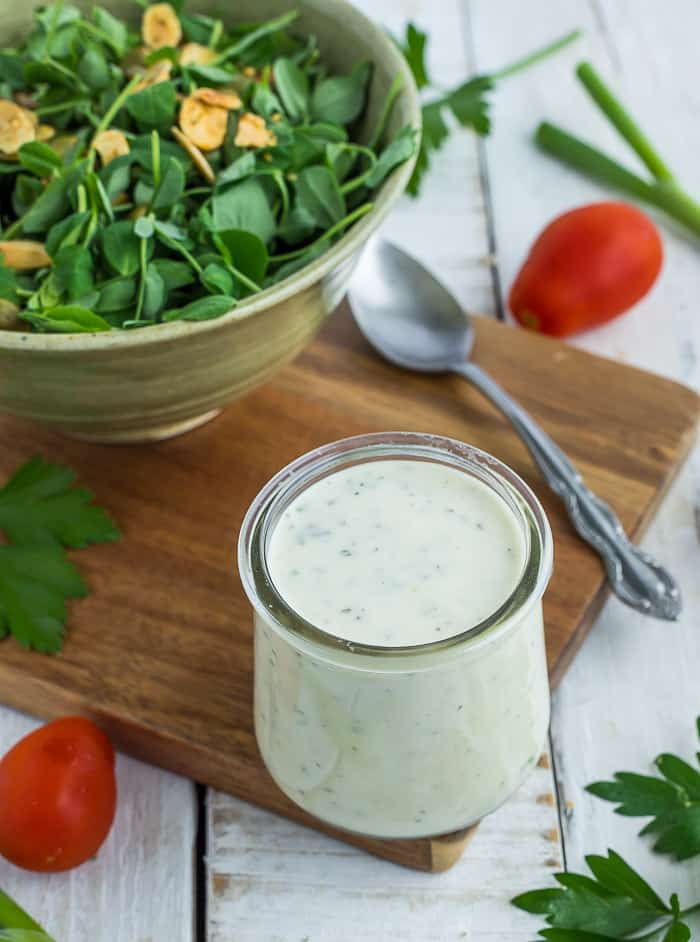 A small glass container of greek yogurt ranch on a wooden cutting board with a salad and vegetables