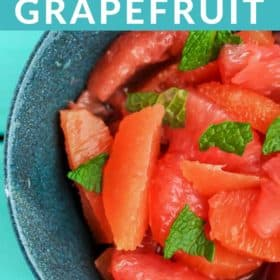 A blue bowl of segemented oranges and grapefruit with sprigs of mint