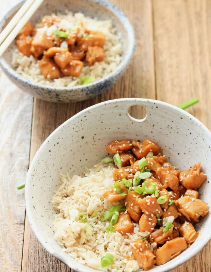 Two bowls of Real Food Instant Pot Orange Chicken with rice on a wooden background