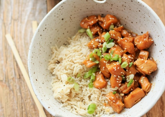 homemade orange chicken and rice in a pottery bowl with chopsticks on a wooden board