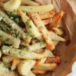 homemade air fry french fries in a bowl with brown paper. Topped with parsley, roasted garlic and parmesan cheese