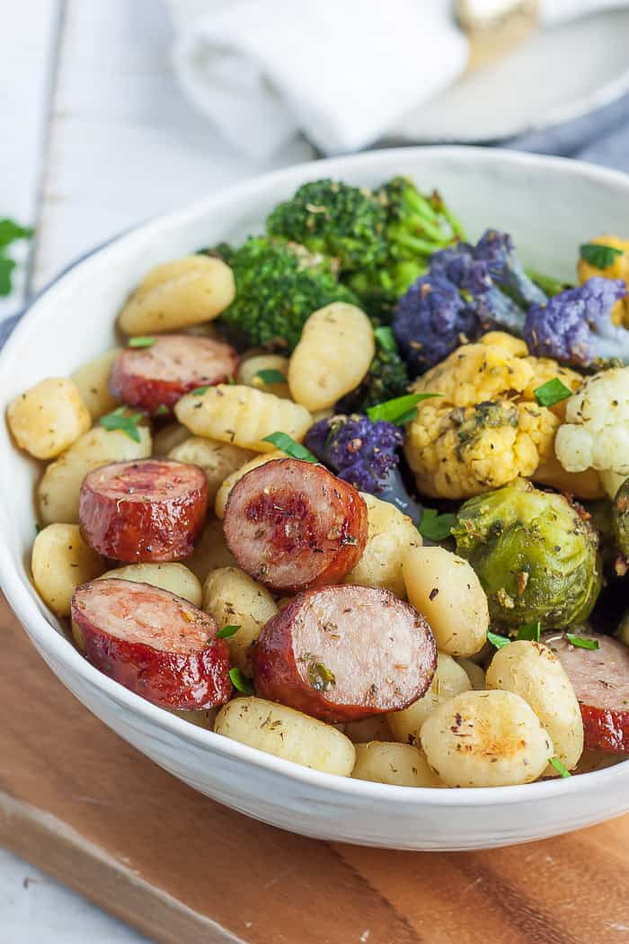 A white bowl full of fried gnocchi, chicken sausage, and roasted veggies