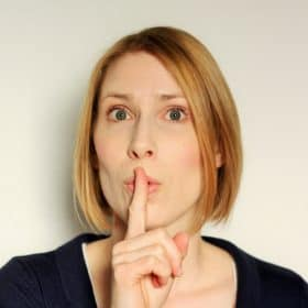 "A woman with a finger up to her mouth saying ""shhhhh"""