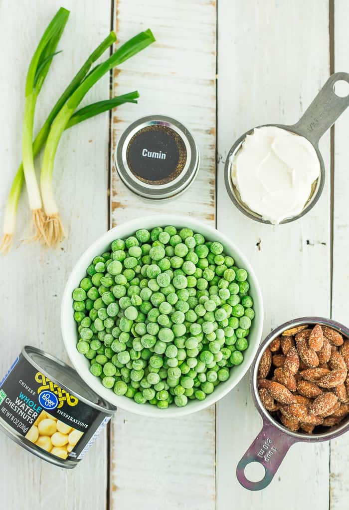 a bowl of peas, green onions, and other ingredients for making green pea salad without mayo