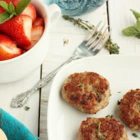 Three sausage patties on a plate with strawberries and herbs in the background
